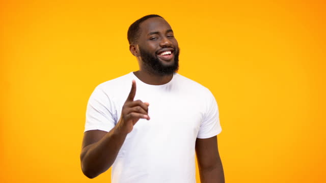 vídeos de stock, filmes e b-roll de homem afro-americano smug que aponta seu dedo consciente de encontro ao fundo amarelo - consciência negra