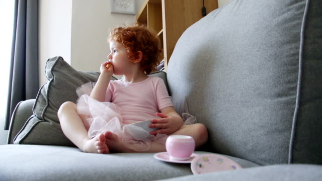 Snacks Fit For a Ballerina Little girl is sitting on the sofa in the living room of her home with some potato snacks. She is dressed up in a ballerina costume and is looking around. potato chip stock videos & royalty-free footage