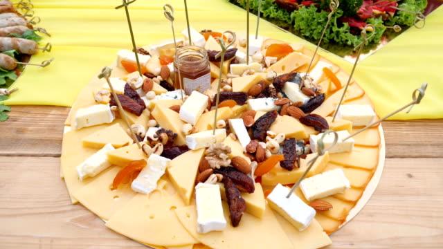 vidéos et rushes de des collations de fromage à pâte dure et fruits séchés sur grande assiette bouchent - pots de bureau