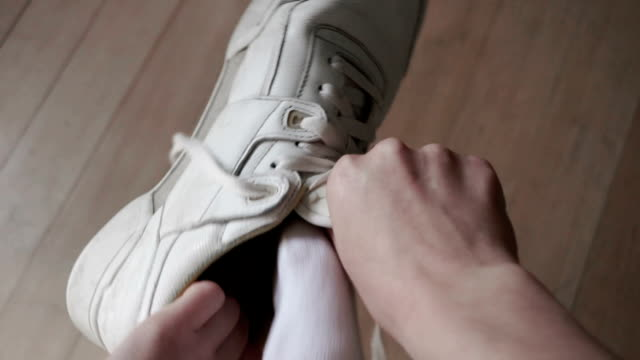 Sneakers on Close up, point-of-view (1st person POV) clip of a young woman putting on a pair of sneakers / trainers. shoe stock videos & royalty-free footage