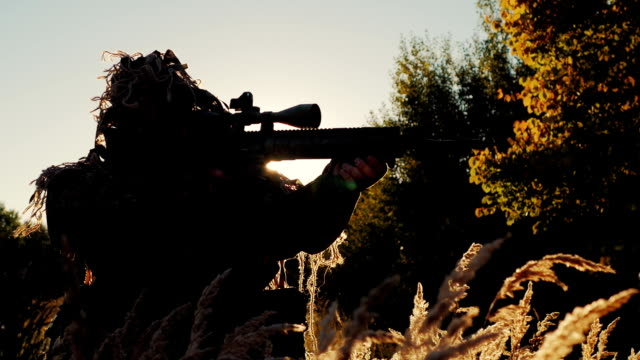 Sniper in camouflage clothing takes aim. The sun's rays shine through in the back and arms video
