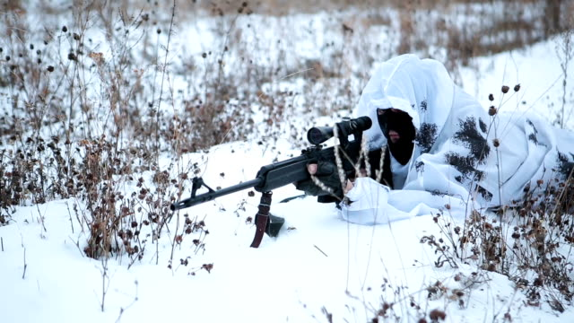 sniper in camouflage lying in the snow and make a shot video