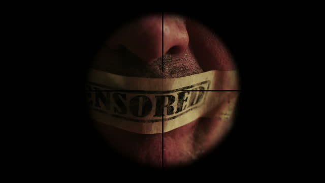Sniper scope on man with tape censored over mouth video