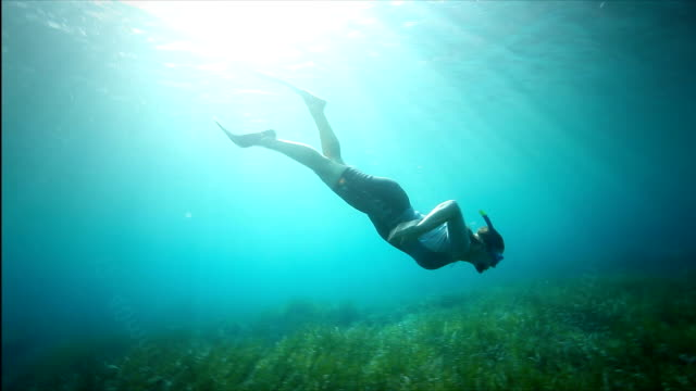 Snorkeling woman HD1080p: Young woman is duck diving and swimming along underwater scuba diving stock videos & royalty-free footage