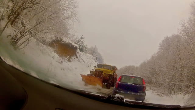 Snow blower removing snow from mountain road video