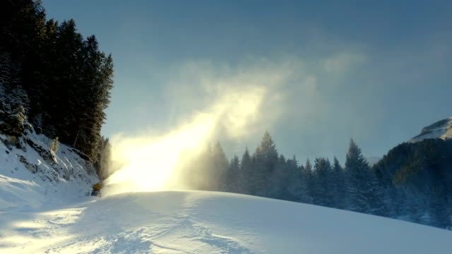 snow cannon making artificial snow on slope against sunrise video