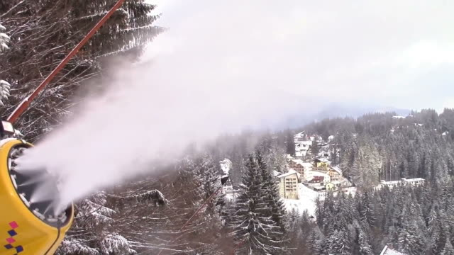 Snow cannon on a ski slope spraying water under pressure and transforming it into artificial snow, with ski resort in background video