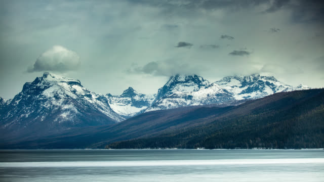 Snow Clouds Blowing Over Lake and Mountains in Glacier National Park - Time Lapse video