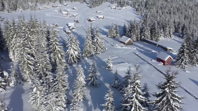 Snow covered remote village, homestead in the mountains. 4K aerial drone view Snow covered remote village, homestead in the mountains. 4K aerial drone view chalet stock videos & royalty-free footage