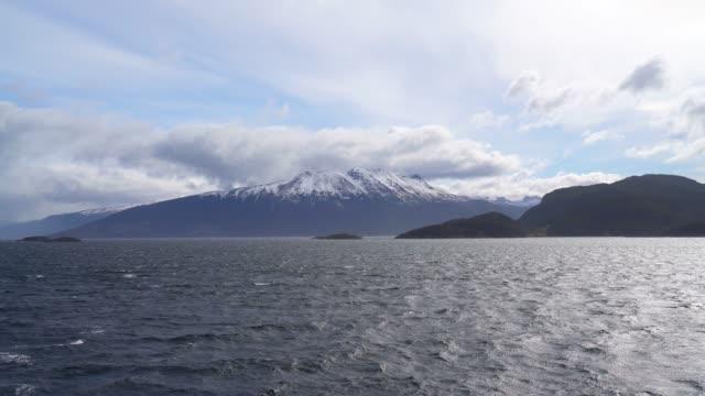 cime innevate su una catena montuosa viste da una nave - argentina america del sud video stock e b–roll