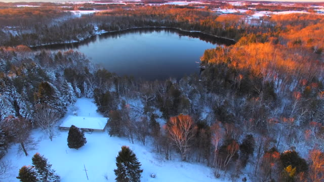 Snow covered woods surround icy lake by light of dawn video
