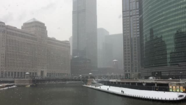 vídeos de stock e filmes b-roll de snow falling across chicago river as commuters brave the weather on the riverwalk. - passagem de ano