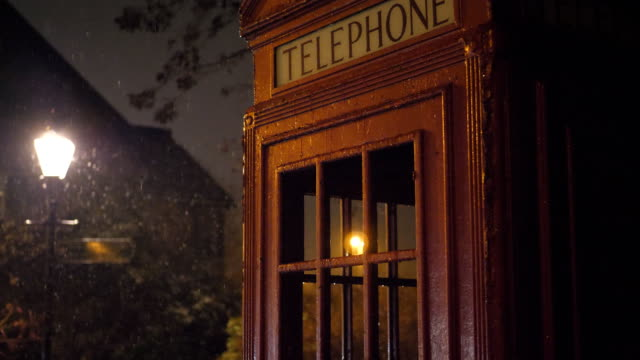 Snow falling on a red telephone booth and a street lantern at night.