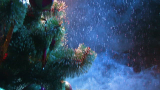 Snow falling on Christmas tree and toys in the smoke video