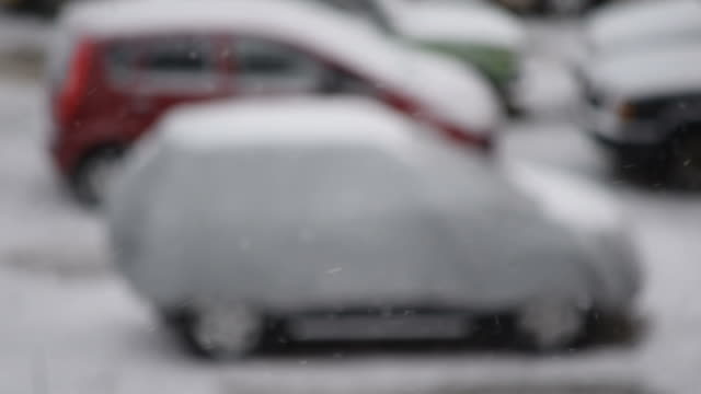 Snow falls on cars parking lot video
