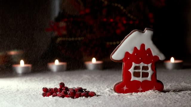 schnee fällt auf das lebkuchenhaus. weihnachtsarrangement auf dem tisch - lebkuchenhaus stock-videos und b-roll-filmmaterial