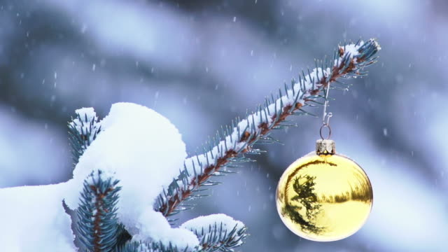 Snow gently falling on Christmas ornament hanging from tree video