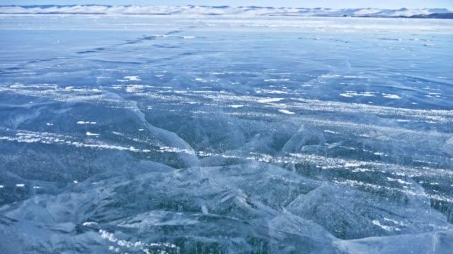 la neve sta sorvolando la superficie del ghiaccio. fiocchi di neve volano sul ghiaccio del lago baikal. il ghiaccio è molto bello con crepe uniche insolite. sfondo vista paesaggio montano. la neve brilla e brilla di rosso. - ghiaccio galleggiante video stock e b–roll