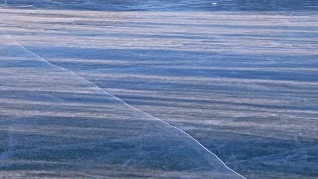 la neve sta sorvolando la superficie del ghiaccio. fiocchi di neve volano sul ghiaccio del lago baikal. il ghiaccio è molto bello con crepe uniche insolite. la neve brilla e brilla di rosso. foto al tramonto. contrasto elevato. - ghiaccio galleggiante video stock e b–roll