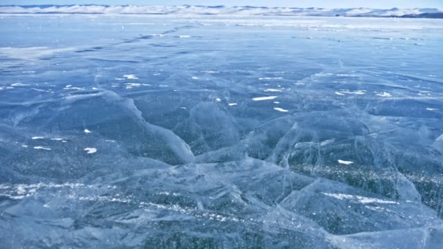 Snow is flying over surface of ice. Snowflakes fly on ice of Lake Baikal. Ice is very beautiful with unusual unique cracks. Background view mountain landscape. Snow sparkles and glows in red.