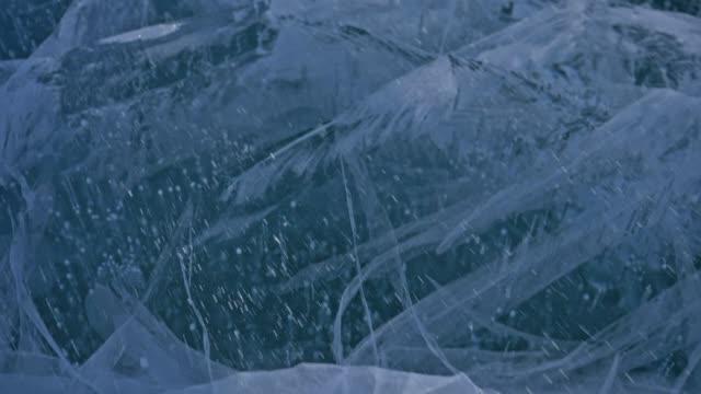 kar buz yüzey üzerinde uçuyor. kar taneleri baykal gölü buz üzerinde uçmak. buz ile olağandışı benzersiz çatlaklar çok güzelmiş. kar parıldıyor ve kırmızı renkte yanıyor. günbatımında resim. yüksek karşıtlık. - donmuş su stok videoları ve detay görüntü çekimi