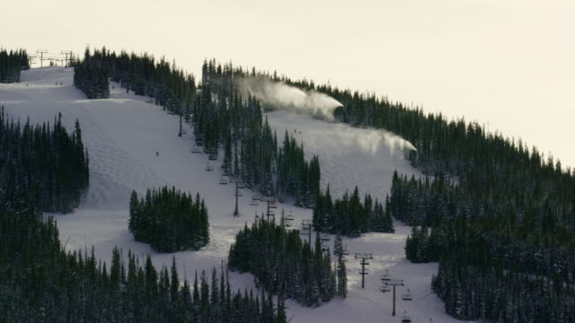 Snow Machines Blow Snow into the Air while People Ski and Snowboard down the Slopes at a Colorado Mountain Ski Resort at Sunset in Winter