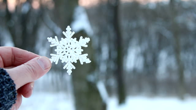 snow or winter concept, hand holding a snowflake