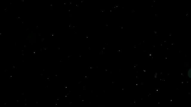 vídeos de stock e filmes b-roll de snow particles falling from the night sky - particles