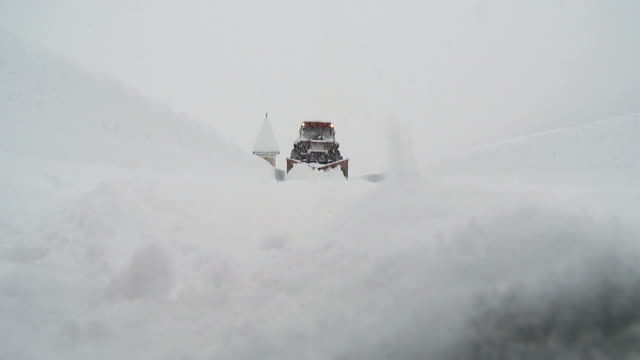 HD: Snow removal HD720p: Shot of tractor with snowplow cleaning country road and approaching to camera on snowy winter day. plow stock videos & royalty-free footage