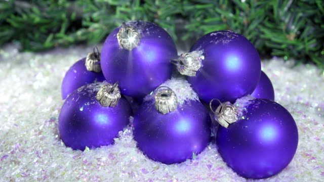 Snow slowly falls on New Year's balls against the background of a Christmas fir-tree video