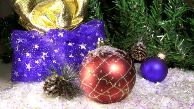 Snow slowly falls on New Year's balls against the background of a Christmas fir-tree. slow motion video