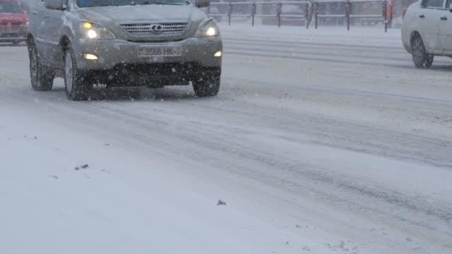 vídeos y material grabado en eventos de stock de tormenta de nieve en la ciudad con condiciones de ventisca. tráfico en la ciudad, durante una fuerte tormenta de nieve. - nieve amontonada