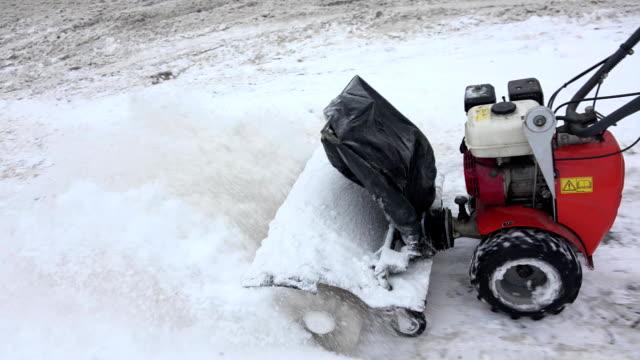 Snowblower clean snow from sidewalk in winter. FullHD video
