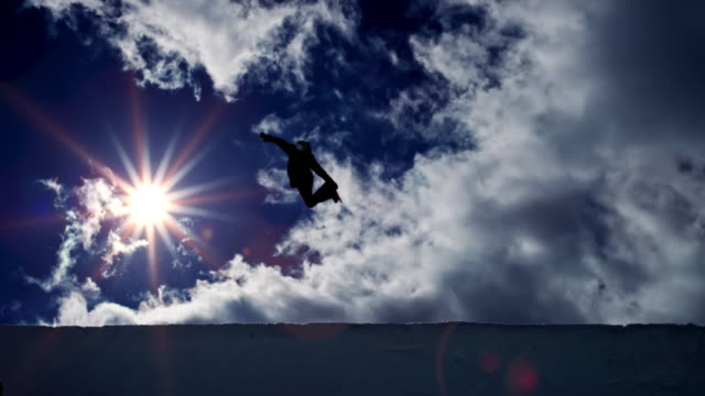 SLO MO LD Snowboarder airborne in the half-pipe with sun in the background