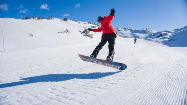 snowboarder at a mountain ski resort riding down the slope, performing a jump trick on the way - snowboarding video stock e b–roll