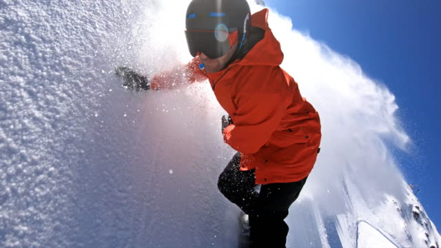 snowboarder carving down the ski slope, leaving a cloud of powder snow behind - snowboarding video stock e b–roll