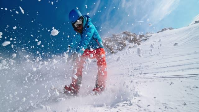 SPEED RAMP Snowboarder cutting through fresh snow in sunshine
