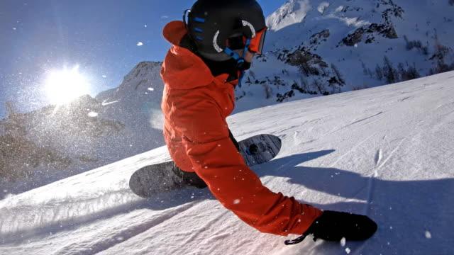 snowboarder extreme carving, spraying snow into camera - сноубординг стоковые видео и кадры b-roll
