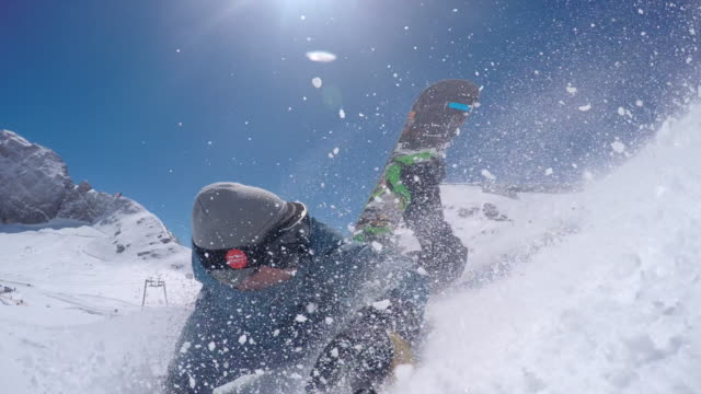 Snowboarder falling while taking a selfie video