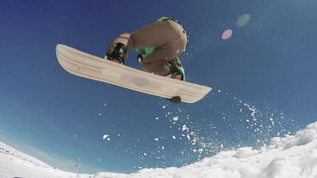 snowboarder jumping against blue sky - snowboarding video stock e b–roll