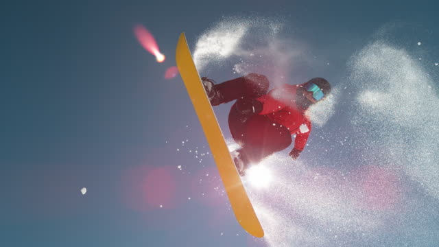 slow motion close up: snowboarder jumping and flying over sun on clear blue sky - sci attrezzatura sportiva video stock e b–roll
