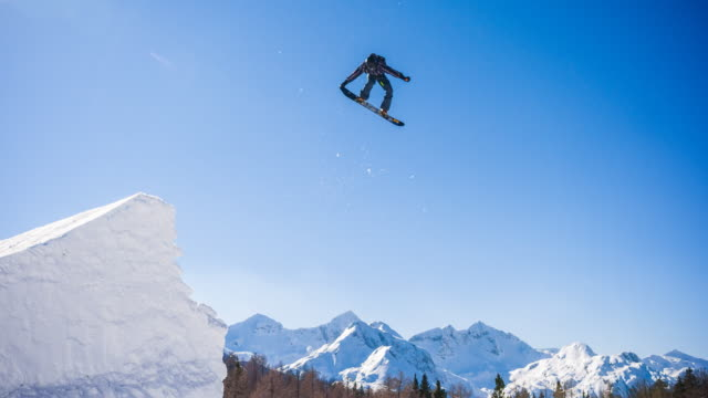 snowboarder jumping in a snowpark - snowboarding video stock e b–roll