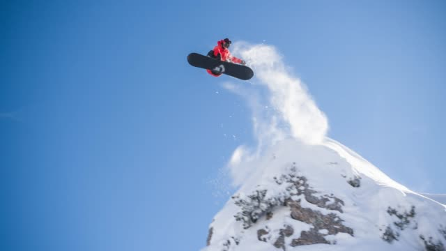 snowboarder jumping off a cliff - snowboarding video stock e b–roll