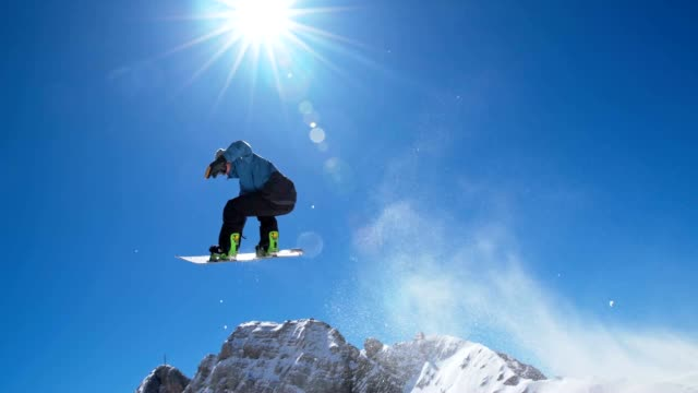 SLO MO Snowboarder jumping over blue clear sky video