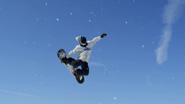 SLOW MOTION CLOSE UP: Snowboarder jumping over the camera in snowpark on a beautiful sunny day in snowy ski resort video