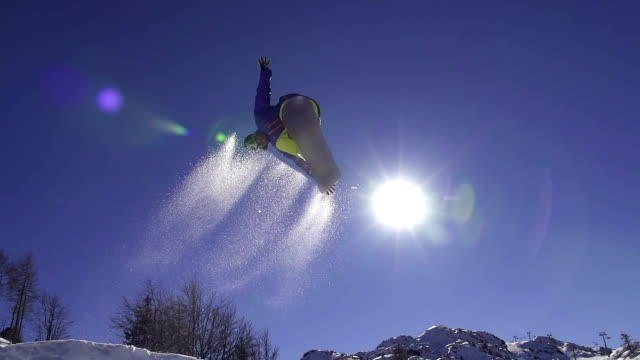 SLOW MOTION: Snowboarder jumping over the sun video