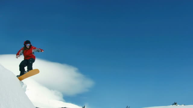 Snowboarder jumps into sky, slow motion video