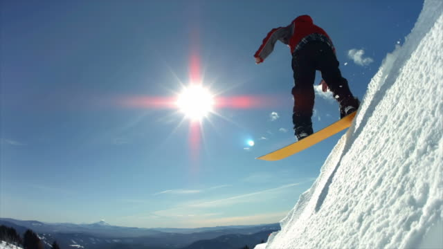 Snowboarder jumps off snow cliff, slow motion video