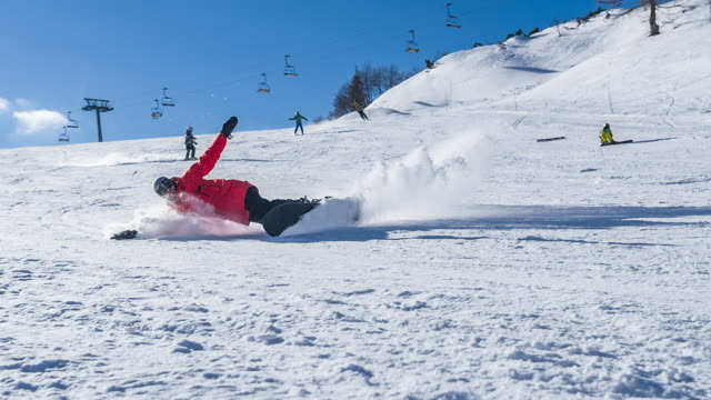 Snowboarder making a turn on ski slope, leaving a cloud of powder snow behind
