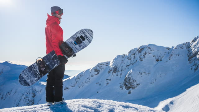 snowboarder on top of mountain enjoying the view of winter landscape on a sunny day - snowboarding video stock e b–roll